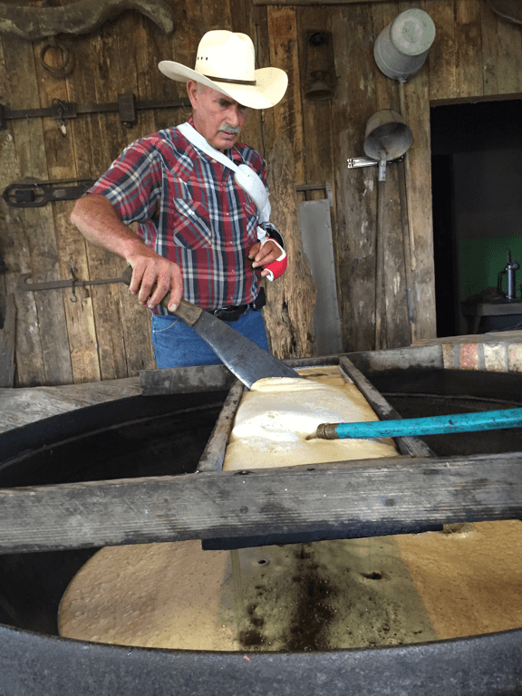 Steve cleans the strainer as the cane juice flows into the cooking kettle.
